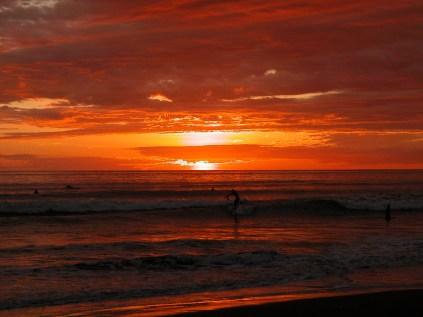Kosta Rika'da pasifik güneş batışı ve sörfçüler